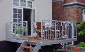 Terrasse med smart gelænder og trappe ned til haven